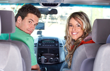 couple looking in backseat at camera